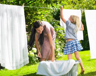 girl-helping-woman-hang-sheets
