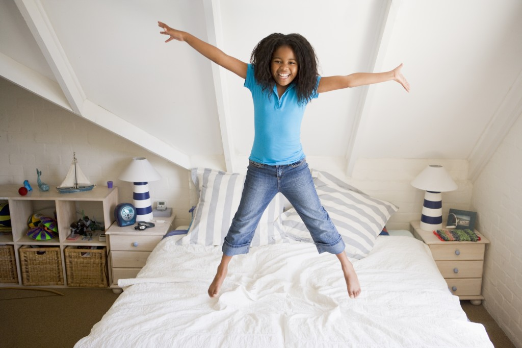 Girl jumping for joy because of her percale sheets