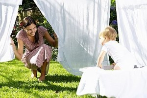 Woman Hanging Sheets With Baby