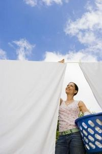 woman-hanging-sheets-laundry-basket-blue-sky-low-angle1