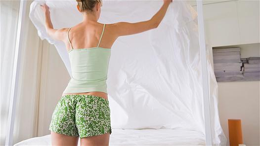 woman-making-bed-shorts-from-the-back
